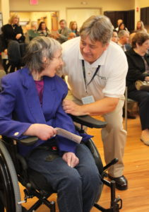 A Beechwood client smiles while speaking with a Beechwood staff member.