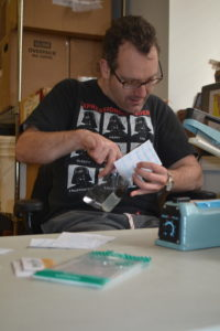 Adam Greene assembles favors for the Social Innovations Awards while working at BeechTree.