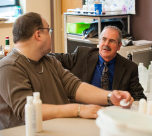 Beechwood Executive Director Dr. Drew Nagele talks with a Beechwood Clubhouse member about his work with BeechTree bath and body products.